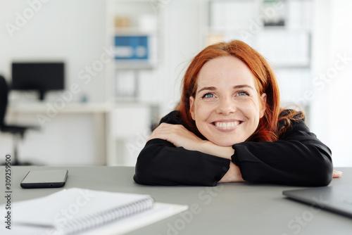 Young businesswoman sitting daydreaming Fototapeta