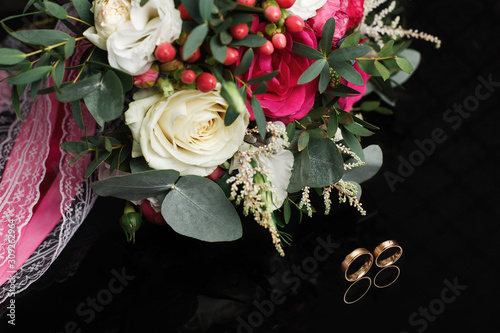 Fototapety, obrazy: Wedding bridal bouquet. Wedding rings in a box on black background. beautiful engagement ring in white gold with engraving close up. wedding day. wedding details.  beautiful floral arrangement