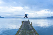 Young Man Jumping On Pier Over...