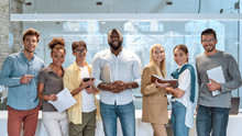 Dream Work. Portrait Of Young And Successful Co-workers In Casual Wear Smiling At Camera While Standing In Working Space