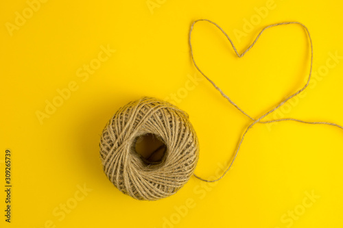Canvastavla  A thread in the shape of the heart on yellow background