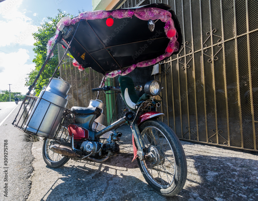 Fototapeta dramatic image of a moter bike converted to a food delivery in the dominican republic.