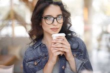 Young Woman Drinking Coffee In...