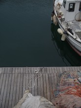 High Angle Shot Of Fishing Nets On An Old Wooden Pier And A Rusty Boat In The Water