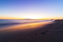 The Beach At The Sunset With Footprints On The Sand
