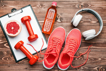 Dumbbells With Clipboard, Shoes, Headphones And Bottle Of Water On Wooden Background