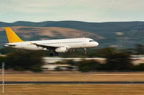 Fototapeta Panning shot of passenger airplane landing on runaway obraz na płótnie
