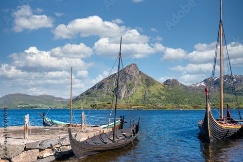 Photo Viking warrior ancient  wooden long ships on harbour with blue cloudy sky and green mountain in the background