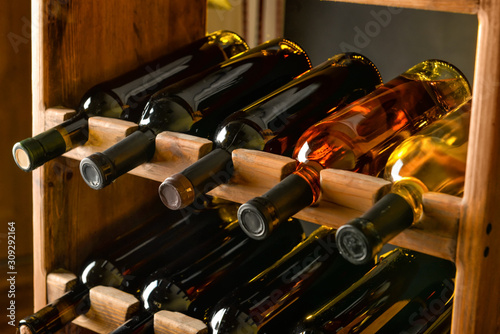 Wooden holder with bottles of wine in cellar Wallpaper Mural