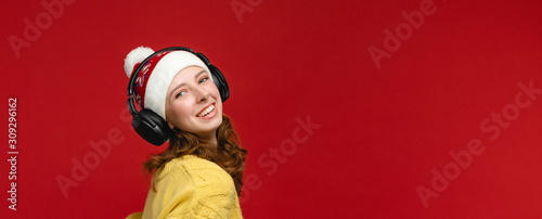 Fototapeta Nice young women in yellow sweater and Christmas hat at the studio on red background