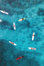 Aerial Pic Of Surfers Seating On Surfboards And Waiting For Wave In The Middle Of Ocean With Perfect Weather And Clean Water At Sunset Time In Hawaii Paradise, Shot On Drone From Above