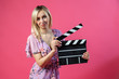 canvas print picture - Beautiful blonde woman in a purple sundress holds an open clapperboard filmmaker in black with white stripes to start shooting a film on a pink isolated background. Film industry.