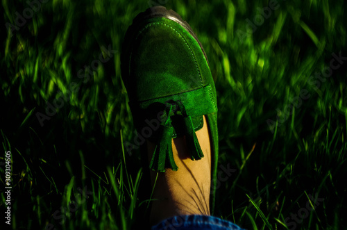 Photo Green suede loafers on grass background. Bokeh. Horizontal