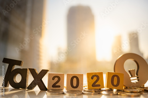 Fototapeta Wood word TAX 2020 and stack of coins on blurred city scape with copy space using as background Income, tax, financial data concept. obraz