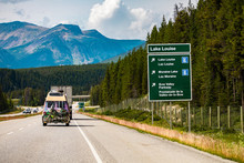 Information Road Green Sign, Lake Louise, Moraine Lake, Bow Valley Parkway, Vehicles On Canadian Road Between Forest Trees, Mountains, Alberta, Canada
