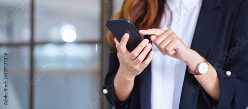 Obraz Closeup image of a businesswoman holding and using mobile phone - fototapety do salonu