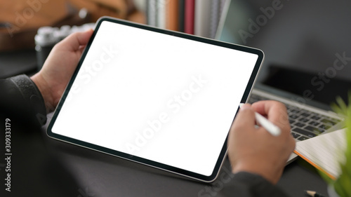 Valokuva Cropped shot of young businessman using blank screen digital tablet in modern of