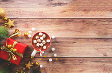 A Cup Hot Chocolate With Marshmallow, Red Gift Box, Pine Cone Decoration And Shining Golden Star Flakes, Copy Space For Merry Christmas And Happy New Year Concept Background.
