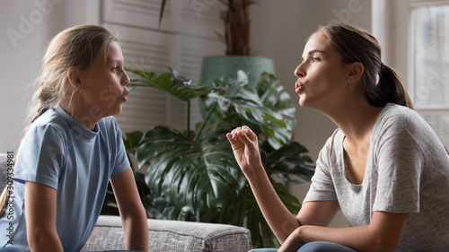 Young mom do pronunciation exercises with daughter Wallpaper Mural