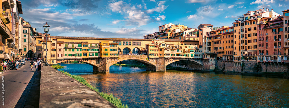 Panoramic view of medieval arched river bridge with Roman origins - Ponte Vecchio over Arno river. Colorful summer cityscape of Florence, Italy, Europe. Traveling concept background.