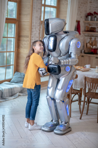 Photo Girl in orange shirt feeling good with her house robot