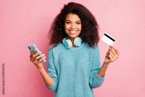 Obraz Close-up portrait of her she nice attractive lovely cheerful cheery wavy-haired girl holding in hands cell bank card wireless purchase buying shopping online isolated over pink pastel color background - fototapety do salonu