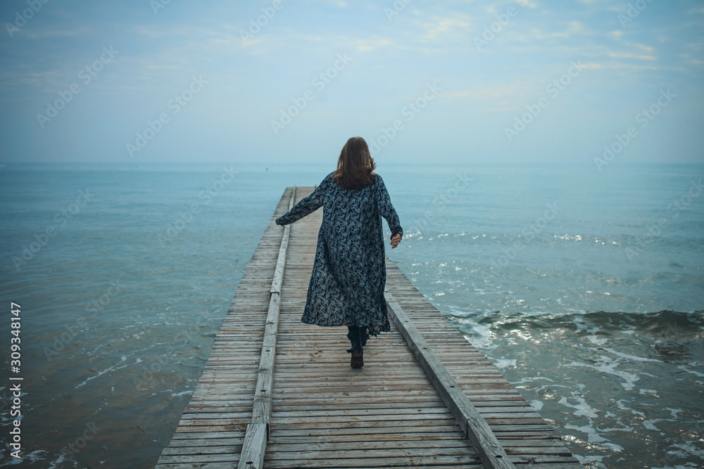 Fototapeta Young Girl Walking on the Pier to the Sea