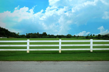 Landscape Of Farm With Split Rail Fence. White Short Fence In The Field. Landscape Farm With Cloudy And Blue Sky.