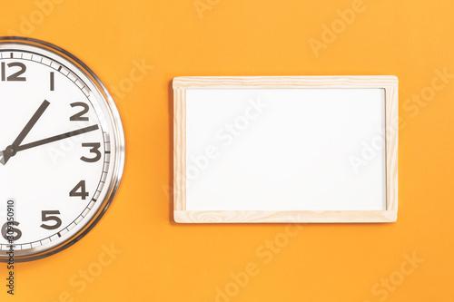 Part of analogue plain wall clock with white board on trendy saffron orange background Tapéta, Fotótapéta