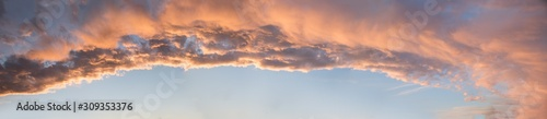 Fototapeta wide dreamy sunset panorama with lighted clouds and blue sky in the lower half obraz