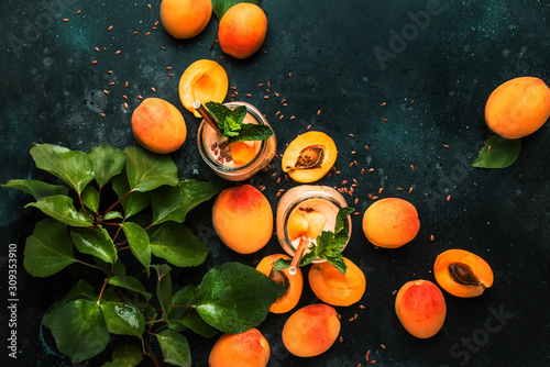 Healthy apricot smoothies in glass bottles and fresh fruits, top view Wallpaper Mural