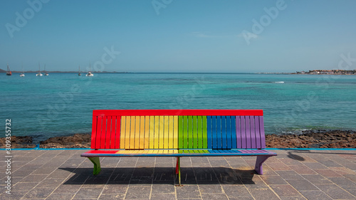 Photo Rainbow bench facing inland in Corralejo, pride colors painted sitting or restin