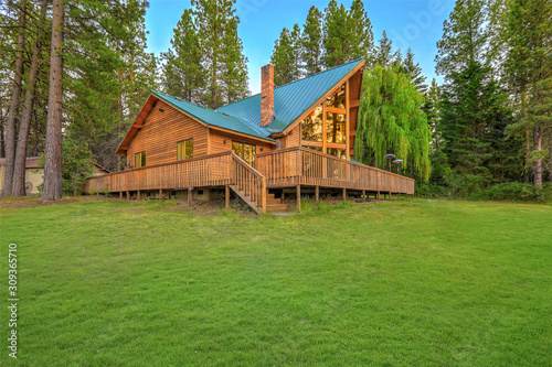 Canvas Print Luxury summer mountain cabin home with large green lawn and pine trees