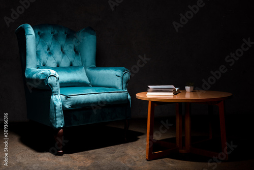 Photo elegant velour blue armchair near wooden table with book isolated on black