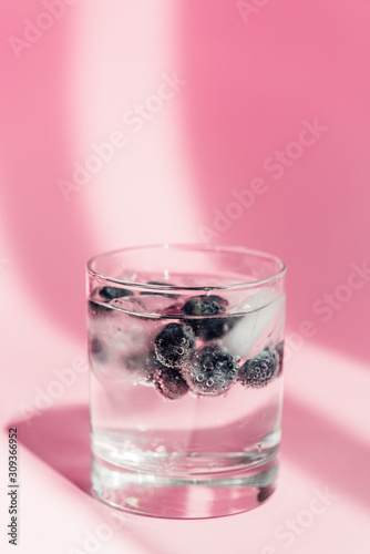 fresh lemonade with ice and blueberries in sunlight on pink background - 309366952