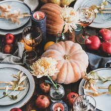 Fall Table Setting For Thanksgiving Day Or Family Gathering Dinner. Plates, Silverware, Floral And Fruits Decoration, Candles And Pumpkins Over Rustic Wooden Table Background, Square Crop