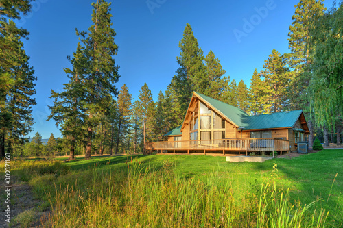 Canvas Print Luxury Cedar cabin home with Large pine tree and pond