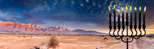 Colorful Sunset In Desert Area Of The Middle East And Menorah With Burning Candles On Foreground . Digital Composite