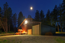 Large Metal Barn At Night With Fire At Round Table And Outdoor Furniture.