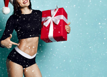 Sporty Woman In Christmas Cap Holding New Year Red Gift Box, Pointing Her Finger At Her Stomach Muscles Under The Snow