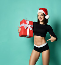 Athletic Woman Brunette In Christmas Cap Holding New Year Red Gift Box, Pointing Her Finger At Her Ideal Stomach Muscles