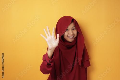 Happy Muslim Teenage Girl Smiling and Waving at Camera Wallpaper Mural