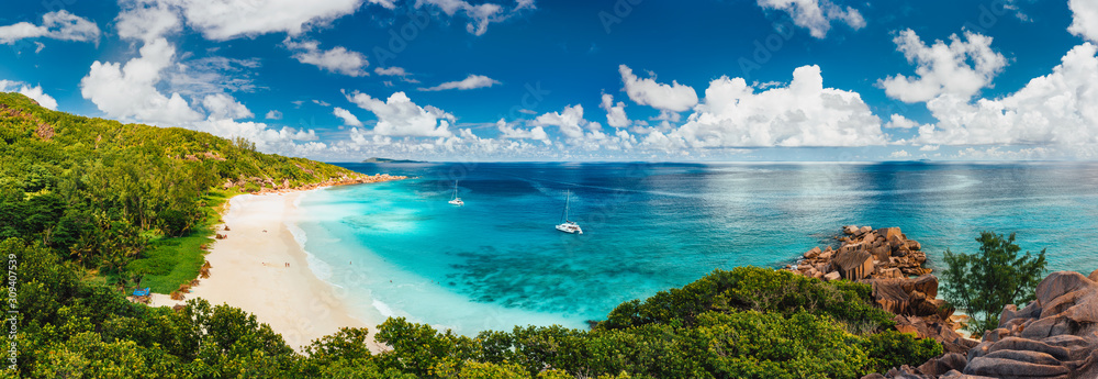 Fototapeta Aerial Pano of Grand Anse beach at La Digue island in Seychelles. White sandy beach with blue ocean lagoon and catamaran yacht moored