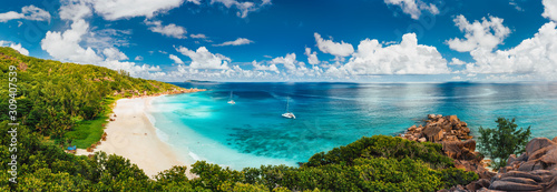 Aerial Pano of Grand Anse beach at La Digue island in Seychelles. White sandy beach with blue ocean lagoon and catamaran yacht moored