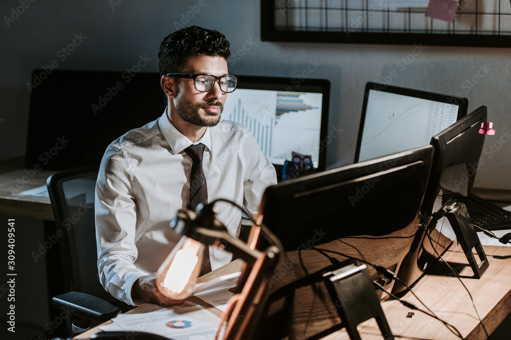 Fototapeta bi-racial trader sitting at table and looking at computer