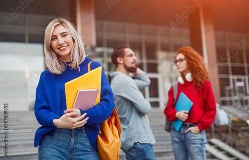 Fotografia Cheerful student standing near classmates outside university