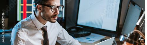 Photo panoramic shot of bi-racial trader in glasses looking at computer