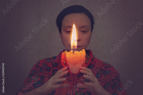 A woman and a burning candle.
