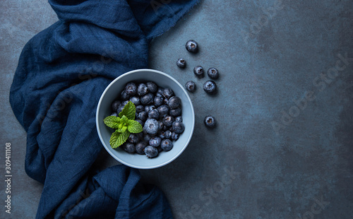 Fresh and sweet blueberry in bowl with classic blue napkin on dark blue wood background