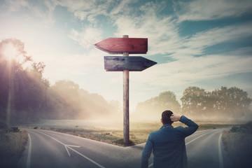 Stražnji poduzetnik ispred strelica križanja i putokaza pokazuje dva različita smjera, lijevi i desni smjer za odabir. Cesta se dijeli u različitim smjerovima. Teška odluka, koncept izbora.